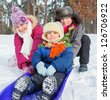 Children on sleds in snow forest. Vertical view. - stock photo