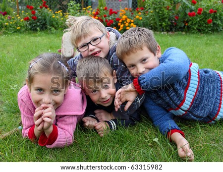 children on the grass, three boys, one girl - stock photo