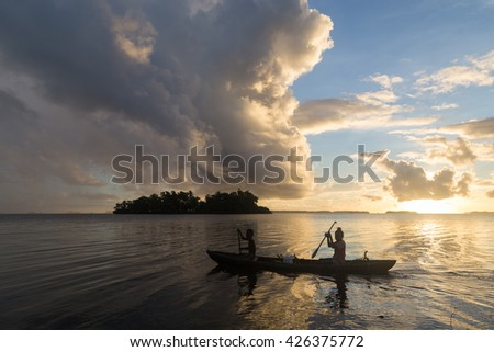 Children on the way to school with a canoe during sunrise in the Solomon Islands. - stock photo