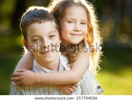 Children outdoors. Happy boy and girl embracing - stock photo