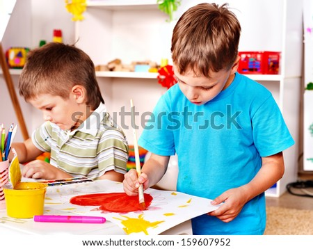 Children painting at easel in school. Education. - stock photo