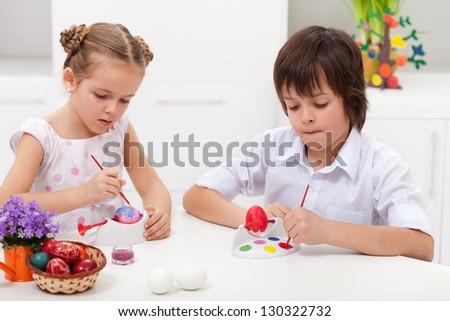 Children painting easter eggs sitting at the table