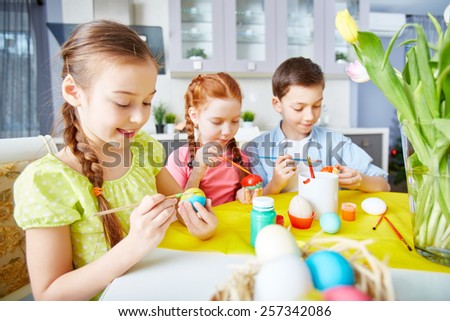 Children painting eggs with gouache - stock photo