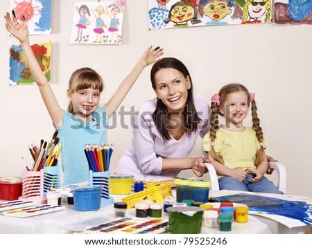 Children painting in preschool. Teacher help by little girl. - stock photo