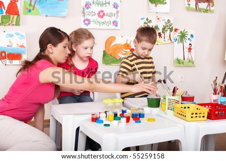 Children painting with teacher in art class. Child care. - stock photo