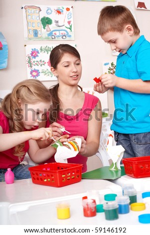 Children painting with teacher in play room. - stock photo