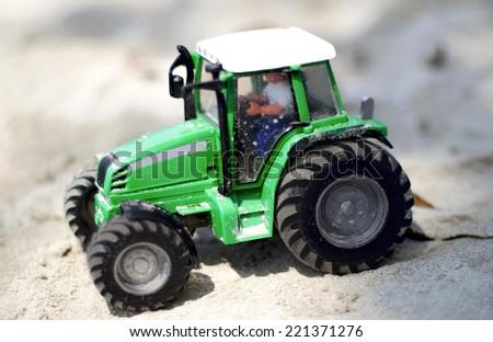Children plastic machine in the sandbox. Toy tractor - stock photo