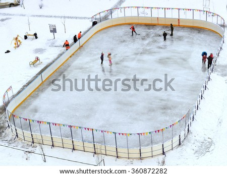 children play hockey and ice-skating at the rink - stock photo