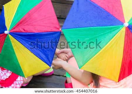 Children play in the rain with umbrellas. Close-up