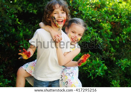 Children play together under the birch. the boy whispered something in the ear of a funny girl. - stock photo