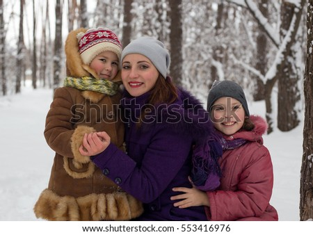 Children play with mom in winter. Two daughters and mom