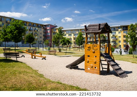 Children playground in nature in front of row of newly built block of flats - stock photo