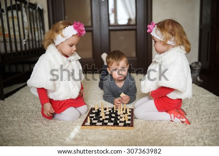 children playing chess lying on the floor - stock photo
