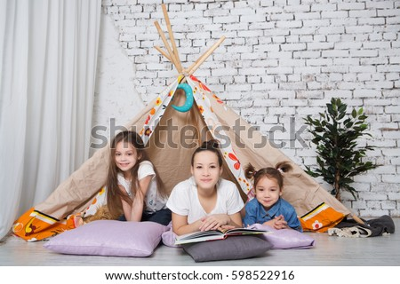 Children playing children room with play tent.  Funny sisters  having fun indoors.