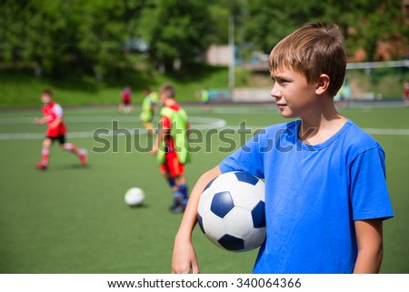 Children playing football in a stadium on a summer day - stock photo