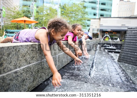 Children playing in a city fountain. Shallow focus on girl's face. - stock photo