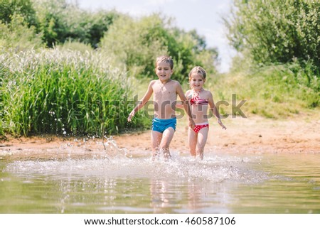 Children playing in a river in hot summer day