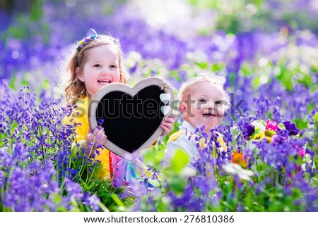 Children playing in bluebell flowers. Little girl and baby boy hold wooden heart shape chalk board. Copy space for your text. Kids having fun outdoors. Birthday or mother's day celebration. - stock photo