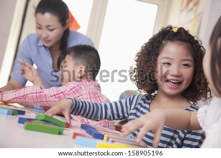 Children playing in classroom - stock photo