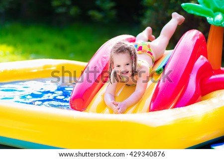 Children playing in inflatable baby pool. Kids swim and splash in colorful garden play center. Happy little girl playing with water toys on hot summer day. Family having fun outdoors in the backyard. - stock photo