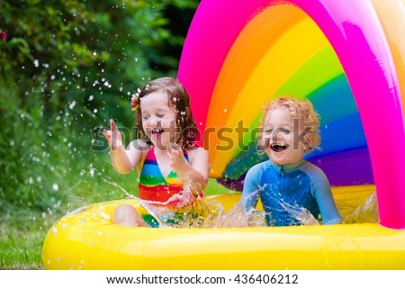 Children playing in inflatable baby pool. Kids swim and splash in colorful garden play center. Happy boy and girl playing with water toys on hot summer day. Family having fun outdoors in the backyard. - stock photo