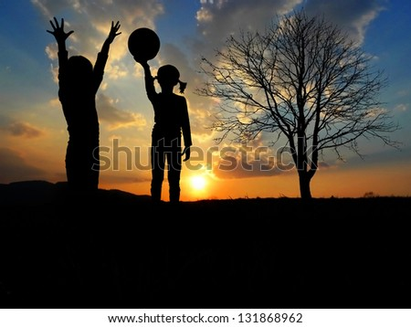 children playing in nature - sunset time - stock photo