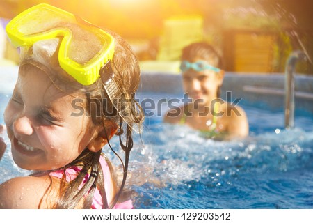 Children playing in pool. Two little girls having fun in the pool. Summer holidays and vacation concept - stock photo