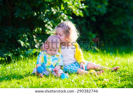 Children playing in the garden. Toddler kid and little baby play outdoors in summer. Girl and boy with toy balls at day care or kindergarten. Child with colorful ball. Outdoor toys for kids. - stock photo