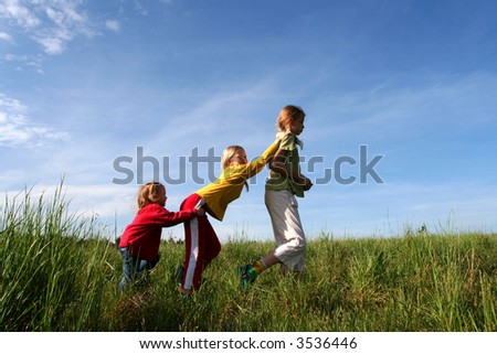 Children playing in the grass on a bue sky background