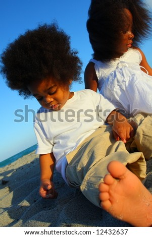 Children playing in the sand with a foot in the foreground - stock photo