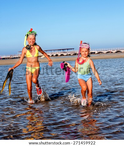 Children playing on  beach. Snorkeling. Raunning on water. - stock photo