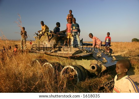 children playing on tank in minefield in Kuito Angola