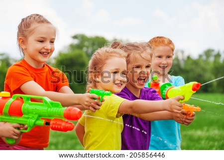 Children playing outdoors with water guns on a beautiful sunny day - stock photo