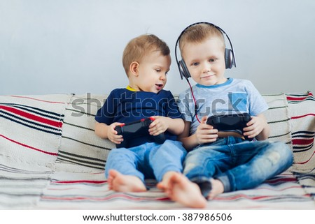 Children playing playstation. Two brothers playing game together - stock photo