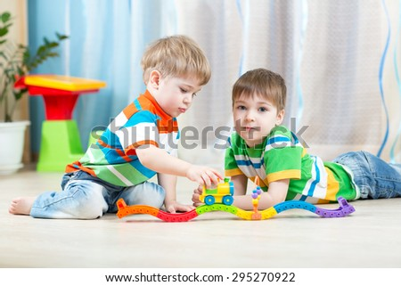 children playing rail road toy in nursery - stock photo