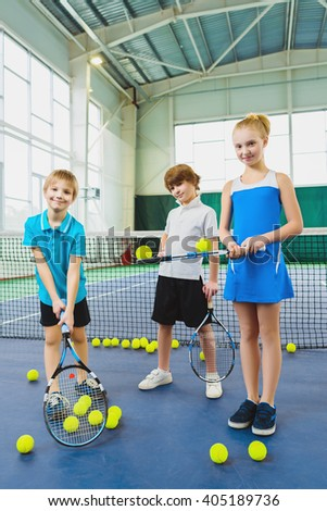 Children playing tennis and posing indoor