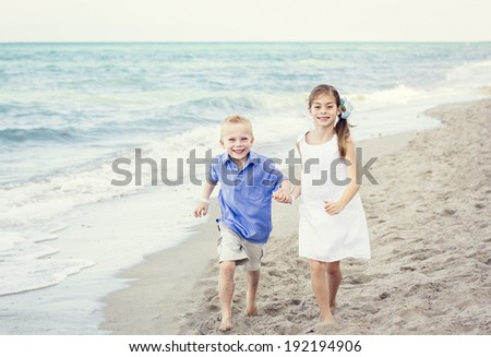 Children playing together along the beach - stock photo