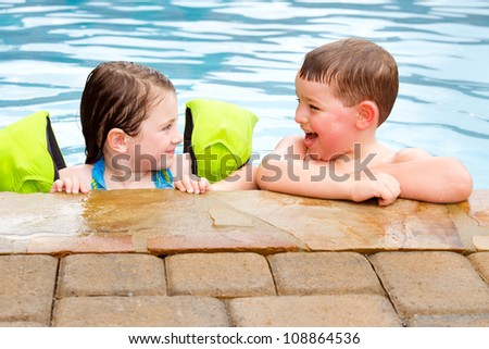 Children playing together laughing and smiling while swimming in pool - stock photo
