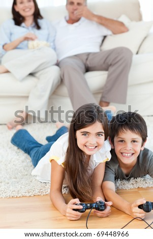 Children playing video games while parents are talking at home - stock photo