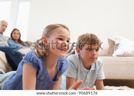 Children playing video games while their parents are watching in a living room - stock photo