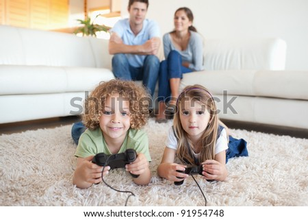 Children playing video games while their parents are watching in their living room - stock photo