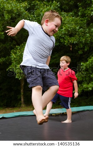 Children playing while jumping on trampoline outdoors on spring day - stock photo