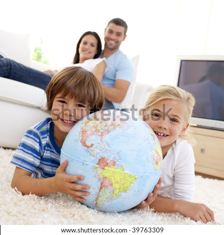 Children playing with a terrestrial globe at home with their parents on sofa - stock photo