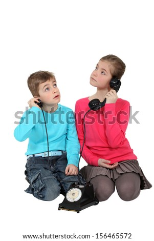 Children playing with an old phone - stock photo