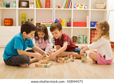 Children playing with blocks on the floor - focus on the boy's face - stock photo