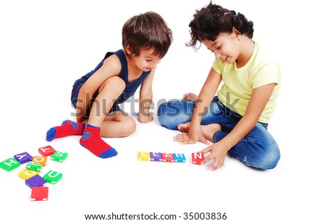 Children playing with cubes in white isolated space - stock photo