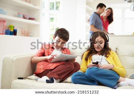 Children Playing With Digital Devices As Parents Make Meal - stock photo