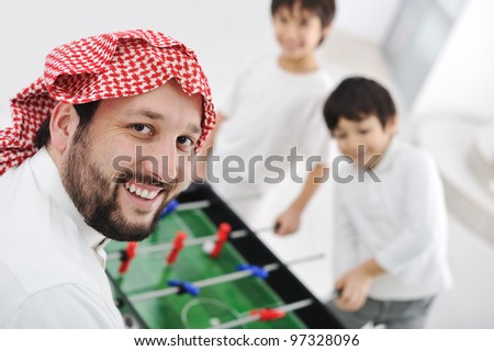 Children playing with father at home, Middle eastern family - stock photo