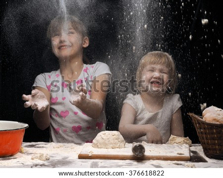 Children playing with flour. Children knead the dough. Girls funny soiled with flour. The kids meal and a table. Very fun game, children are happy - stock photo
