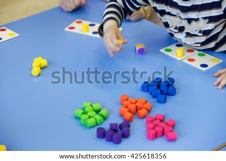 Children playing with homemade, do-it-yourself educational toys, arranging and sorting colors. Learning through experience concept, intelligence development, educational approach concept. - stock photo